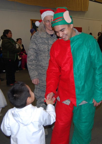 QAANAAQ, Greenland – Tech. Sgt. Oscar Nunez, 821st Air Base Group at Thule Air Base, Greenland, shakes the hand of a child during Operation Julemond in the local community of Qaaanaaq, Dec. 22, 2016. Village families gather every year to celebrate the international relationship with songs around the Christmas tree, hugs, laughter and gifts. (U.S. Air Force photo by Tech. Sgt. Shawn Joseph)