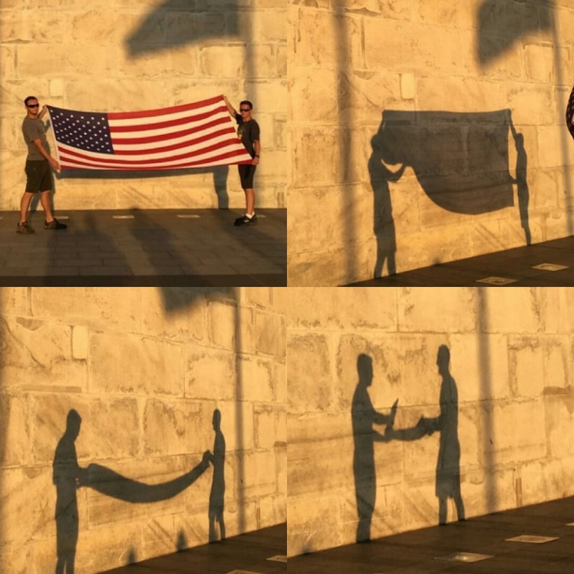 Staff Sgt. Jonathan Balko, an electrical and environmental craftsman assigned to the 28th Aircraft Maintenance Squadron, left, folds his American flag in front of the Washington Monument in Washington, D.C. From a young age, Balko knew he wanted to have a career related to military aviation. (Courtesy photo)