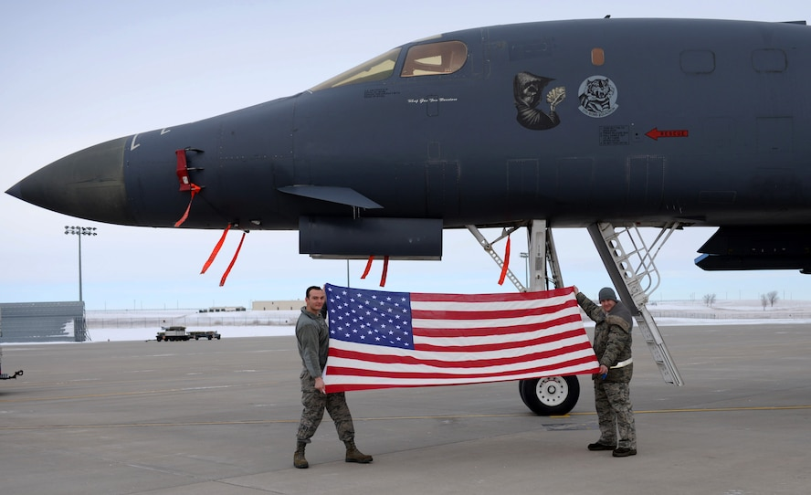 Staff Sgt. Jonathan Balko, an electrical and environmental craftsman assigned to the 28th Aircraft Maintenance Squadron, left, holds up his American flag in front of a B-1 bomber at Ellsworth Air Force Base, S.D., Jan. 4, 2017. Balko first received his flag while on his first deployment to Al Udeid Air Base, Qatar, and since then has taken it to every place he visits, tracking its presence in more than 20 locations. (U.S. Air Force photo by Airman 1st Class Denise M. Jenson)