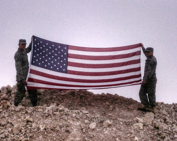 Staff Sgt. Jonathan Balko, an electrical and environmental craftsman assigned to the 28th Aircraft Maintenance Squadron, left, holds up his American flag at a deployed location. From a young age, Balko knew he wanted to have a career related to military aviation. (Courtesy photo)