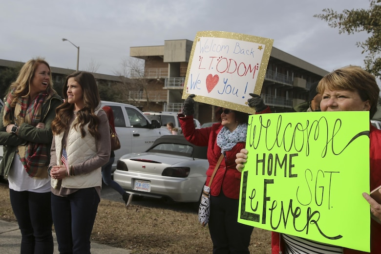 Family and friends of Marines and sailors hold up their signs as the buses carrying their loved ones arrive at Camp Lejeune, N.C., Jan. 10, 2017. Marines and sailors returned after completing the mission of protecting U.S. personnel, property and interests in Europe and Africa as part of a nine-month deployment with Special Purpose Marine Air-Ground Task Force Crisis Response-Africa. The Marines and sailors arriving are with Combat Logistic Battalion 2. (U.S. Marine Corps photo by Lance Cpl. Miranda Faughn)