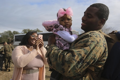 A sailor holds his daughter for the first time at a homecoming at Camp Lejeune, N.C., Jan. 10, 2017. Marines and sailors with Special Purpose Marine Air-Ground Task Force Crisis Response-Africa returned home after completing the mission of protecting U.S. personnel, property and interests in Europe and Africa. The Marines and sailors returning are with Combat Logistics Battalion 2. (U.S. Marine Corps photo by Lance Cpl. Miranda Faughn)