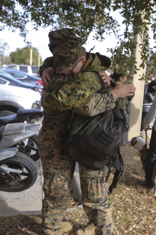 Marine buddies hug each other after returning from a nine-month deployment with Special Purpose Marine Air-Ground Task Force Crisis Response-Africa at Camp Lejeune, N.C., Jan. 10, 2017. The SPMAGTF-CR-AF mission is to protect U.S. personnel, property and interests in Europe and Africa. The Marines and Sailors returning are with Combat Logistics Battalion 2. (U.S. Marine Corps photo by Lance Cpl. Miranda Faughn)