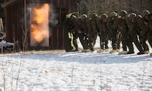 Marines with Weapons Company, 3rd Battalion, 25th Marine Regiment, 4th Marine Division, take cover as a doughnut charge is used to breach a building during exercise Nordic Frost at Camp Ethan Allen Training Site in Jericho, Vt., Jan. 7. 2017. The Marines were evaluated on their ability to successfully operate the demolitions in a demanding cold-weather environment. (U.S. Marine Corps photo by Cpl. Melissa Martens/ Released)
