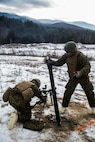 Pfc. Connor R. Leahy (left), and Lance Cpl. Nicholas T. Sams, mortar Marine, for Weapons Company, 3rd Battalion, 25th Marine Regiment, 4th Marine Division, load and fire 81mm mortar rounds during exercise Nordic Frost at Camp Ethan Allen Training Site in Jericho, Vt., Jan. 7. 2017. Throughout the exercise, Marines conduct training in a demanding cold- weather environment that places an emphasis on small-unit leadership. (U.S. Marine Corps photo by Cpl. Melissa Martens/ Released)