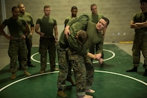 JERICHO, Vt.—Gunnery Sgt. Brandon D. Harris (center), assistant operations chief, Headquarters and Service Company, 3rd Battalion, 25th Marine Regiment, 4th Marine Division, and a black-belt martial arts instructor/trainer, demonstrates how to properly conduct a hip throw during a MCMAP course at exercise Nordic Frost at Camp Ethan Allen Training Site in Jericho, Vt., Jan. 8. 2017. Marines were provided the opportunity to obtain their grey or green belts during the exercise. (U.S. Marine Corps photo by Cpl. Melissa Martens/ Released)
