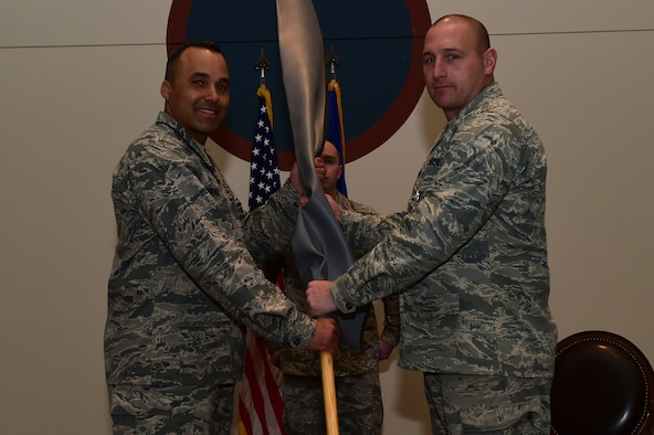 Lt. Col. Craig Thorstenson, 460th Operations Group, Detachment 1 commander, passes the rolled up guidon to Col. Lorenzo Bradley, 460th Operations Group commander, during the 460th OG Det. 1 deactivation ceremony Jan. 11, 2017, at the Leadership Development Center on Buckley Air Force Base, Colo. In 2013 and 2015, Det. 1 was the winner of the General Seth J. McKee Award, which is awarded to the best missile warning unit. (U.S. Air Force photo by Airman 1st Class Gabrielle Spradling/Released)