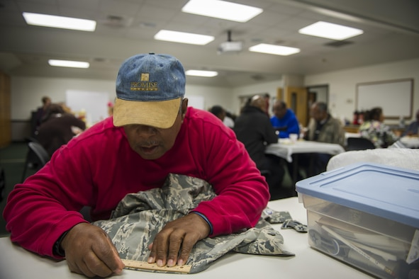Jimmie Thomas, a Munch n' Mend volunteer, measures the sleeve of an Airman battle uniform coat at Hurlburt Field, Fla., Jan. 9, 2016. Thomas has been volunteering with Munch 'n Mend for more than 20 years. Munch n' Mend is a free monthly event where Air Commandos of all rank, enlisted and officer, can take their uniforms to get rank, badges, name and Air Force tapes sewn on while enjoying a hot meal. (U.S. Air Force photo by Airman 1st Class Joseph Pick)