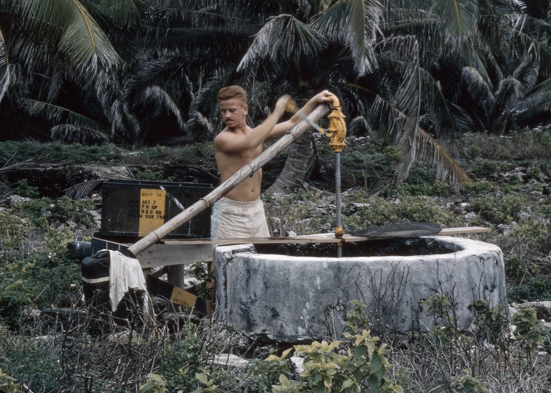 Airman 2nd Class Bob 'Red' Cunningham, of the 1374th Mapping and Charting Squadron, pumps water from an old well on North Danger Island in 1956. The Airmen only used this for laundry and washing. Drinking water was delivered in 55-gallon barrels. (Courtesy photo/Bob Cunningham)