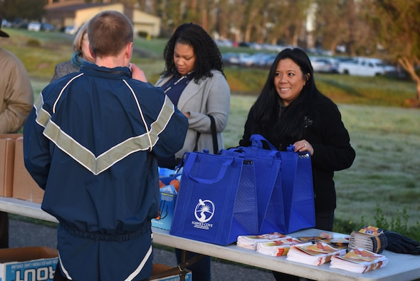 Pauline Chui, 30th Space Wing community support coordinator, speaks with an Airman about the Resilience Race program during the monthly wing run, Jan. 6, 2017, Vandenberg Air Force Base, Calif. The incentive-based program will provide personnel a chance to learn more about helping agencies on Vandenberg, in addition to earning a prize once completed. (U.S. Air Force photo by Senior Airman Robert J. Volio/Released)