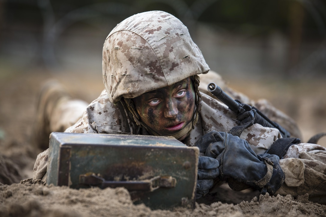 Maria Daume, a Marine Corps recruit, pushes an ammunition can during a 54-hour culminating training event