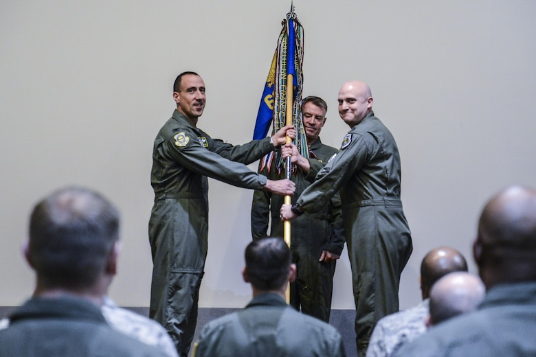 Col. Leonard Kosinski, 62nd Airlift Wing commander, presents the 62nd Operations Group guidon to Lt. Col. Brian Smith, incoming 62nd OG commander during a ceremony Jan. 6, 2017, at Joint Base Lewis-McChord, Wash. The passing of the guidon is a military tradition signifying the official assumption of command.