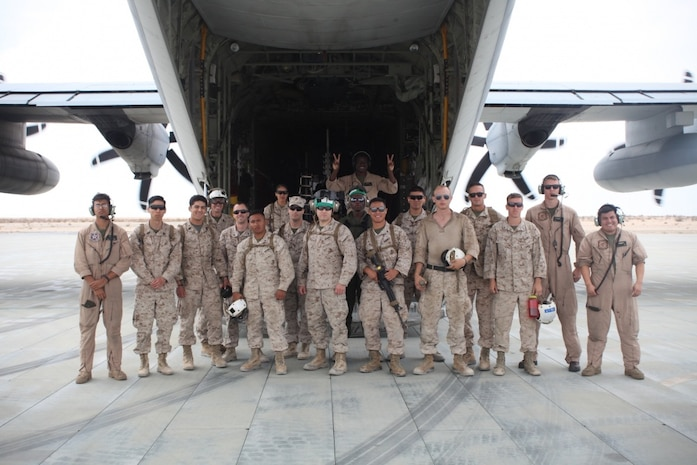 MARINE GROUND AIR COMBAT CENTER TWENTYNINE PALMS, CALIF., -- Marine Aircraft Group 41 Marines and sailors and Marine Aerial Refueler Transport Squadron 234 pose for a group photo outside a C-130 after a morale flight aboard Marine Ground Air Combat Center Twentynine Palms, Calif., June 21, 2016. The morale flight was an invitation extended to MAG-41 to view an aerial refueling of two F/A-18 jets.