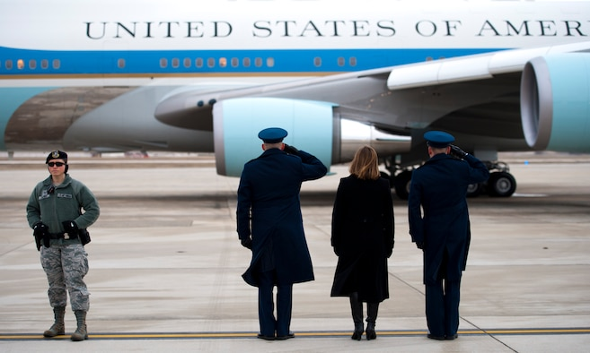 Col. Christopher Thompson (center), 89th Airlift Wing vice commander, his wife (center right), Shannon, and Tech. Sgt. Brian Greene (right), Special Airlift Mission passenger services agent, stand at attention as Air Force One taxis with the president to the runway for takeoff at Joint Base Andrews, Md., Jan. 10, 2017. Staff Sgt. Heather Alred (left), 811th Security Forces Squadron detail chief, maintained a watchful eye on the perimeter of the flightline until the aircraft was airborne. (U.S. Air Force photo by Staff Sgt. Joe Yanik)