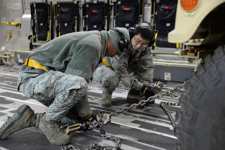 Airmen 1st Class Marcus Downey and Kewei Yu, 43rd Air Mobility Squadron porters, secure a Humvee to the deck of a C-17 Globemaster III during a Deployment Readiness Exercise on Pope Army Airfield Jan. 9, 2017. As part of the exercise, the 43rd AMS brought cargo to the flightline, loaded and then unloaded the aircraft to test the 43rd Air Mobility Operations Group on how they prepare and load cargo for deployment. (U.S. Air Force photo by Master Sgt. Thomas J. Doscher/released)