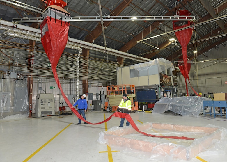 Containment pools (bottom right) were built with wood framing and plastic sheets to aid in water collection during the test. This is a different approach from previous tests where water or fire-fighting foam was released into the hangar after all equipment was manually covered up with plastic. (U.S. Air Force photo by Kenji Thuloweit)