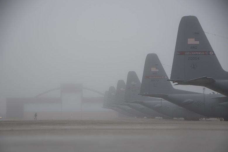 Master Sgt. Kristopher Wolf walks through a blanket of fog settled over a fleet of C-130H Hercules on the 179th Airlift Wing's flightline in Mansfield, Ohio, Jan. 3, 2017. The 179th AW is always on a mission to be the first choice to respond to community, state and federal missions with a trusted team of highly qualified Airmen. (U.S. Air National Guard photo/Tech. Sgt. Joe Harwood)