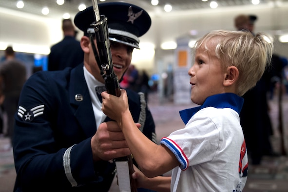 Senior Airman Angelo Hightower, a U.S. Air Force Honor Guard Drill Team member, lets a young boy hold a drill rifle at the Live on Green event in Pasadena, Calif., Dec. 30, 2016. The M-1 Garand rifles weigh about 12 pounds and have dull bayonets attached at their tips. (U.S. Air Force photo/Senior Airman Philip Bryant)