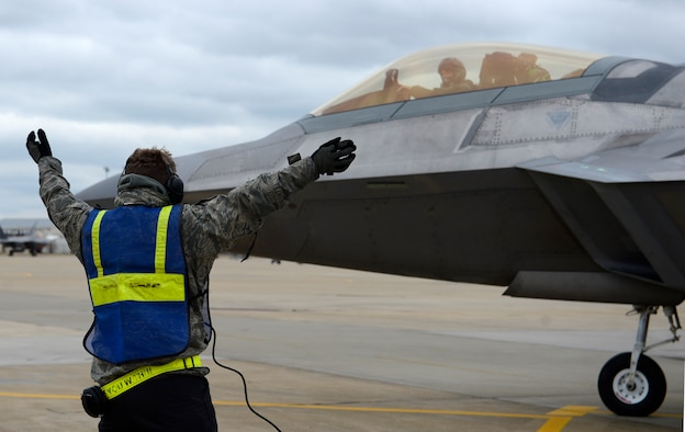 U.S. Air Force Senior Airman Jakob Miner, 1st Aircraft Maintenance Squadron crew chief, signals an F-22 Raptor to stop at a hydrogen pit for a hot pit refuel at Joint Base Langley-Eustis, Va., Jan. 6, 2017. Hydrogen pits are connected to underground pipes that allow fuel to flow from nearby storage tanks. (U.S. Air Force photo by Airman 1st Class Kaylee Dubois)