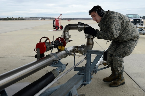 U.S. Air Force Airman Anthony Sanchez, 733rd Logistics Readiness Squadron fuels distribution operator, moves a fuel line in place during a hot pit refuel at Joint Base Langley-Eustis, Va., Jan. 6, 2017. Hot pits which can be done in less than 20 minutes, allowing aircraft to quickly launch after refueling. (U.S. Air Force photo by Airman 1st Class Kaylee Dubois)