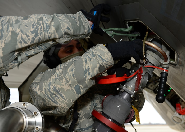 A U.S. Air Force 1st Aircraft Maintenance Squadron crew chief tightens the fuel line nozzle to the F-22 Raptor's fuel tank during a hot pit refuel at Joint Base Langley-Eustis, Va., Jan. 6, 2017. Hot pits are performed while the engine of the plane is running to allow aircraft to launch quickly after refueling. (U.S. Air Force photo by Airman 1st Class Kaylee Dubois)