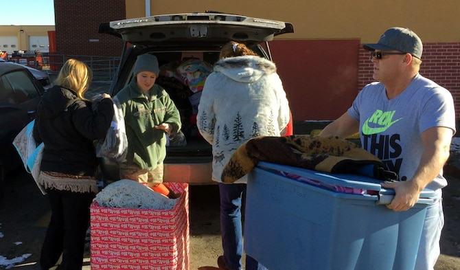 Volunteers from Ellsworth Air Force Base unload donated blankets at the Cornerstone Rescue Mission in Rapid City, S.D., Dec. 19, 2016.  Both the Hope Center and Cornerstone accept donations of many items such as food, clothing, blankets, baby products, and hygiene products for those in need. (Courtesy photo)