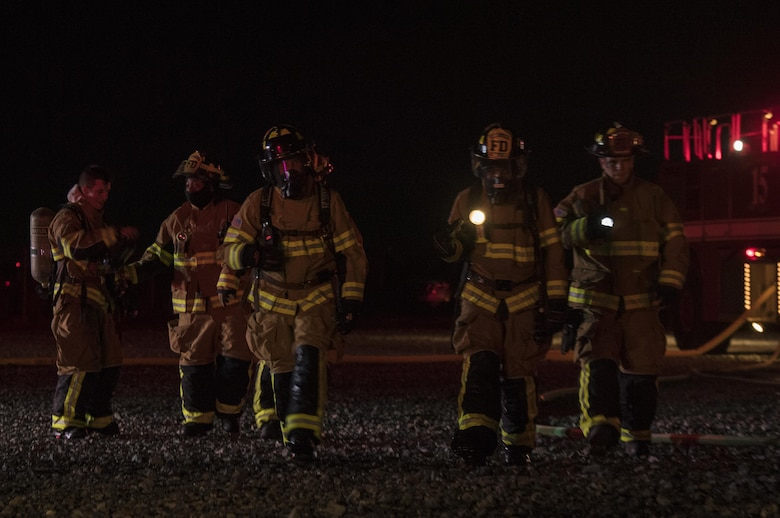 Firefighters from the 23d Civil Engineer Squadron begin to congregate after completing nighttime, live-fire training, Jan. 10, 2017, at Moody Air Force Base, Ga. It's required by the Federal Aviation Administration that every airfield have a firefighting team on standby in case of an aircraft incident. (U.S. Air Force photo by Airman 1st Class Daniel Snider)
