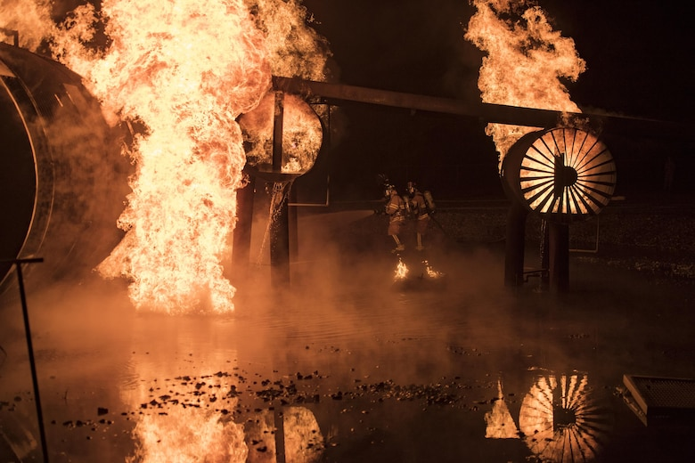 Firefighters from the 23d Civil Engineer Squadron douse flames during nighttime, live-fire training, Jan. 10, 2017, at Moody Air Force Base, Ga. All of Moody's firefighters are required to perform this training at least once a year. (U.S. Air Force photo by Airman 1st Class Daniel Snider)