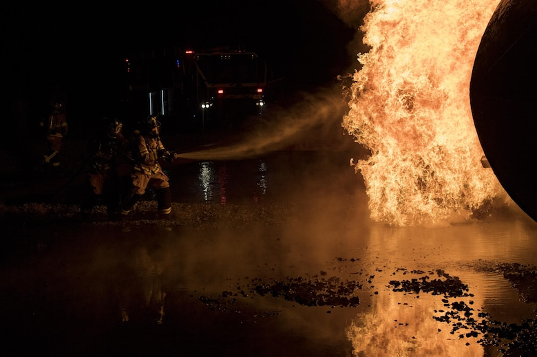 Firefighters from the 23d Civil Engineer Squadron team up to extinguish flames during nighttime, live-fire training, Jan. 10, 2017, at Moody Air Force Base, Ga. The prop aircraft fires were propane-controlled by the fire department's assistant chief of training, Charlie Johnson. (U.S. Air Force photo by Airman 1st Class Daniel Snider)