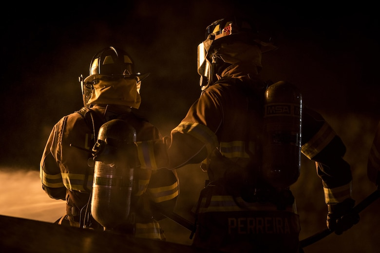 Matthew Perreira, right, 23d Civil Engineer Squadron firefighter, backs up a fellow firefighter during nighttime, live-fire training, Jan. 10, 2017, at Moody Air Force Base, Ga. This training is an annual requirement for Moody firefighters and is just one of the ways they stay ready to protect people, property and the environment from fires and disasters. (U.S. Air Force photo by Staff Sgt. Ryan Callaghan)
