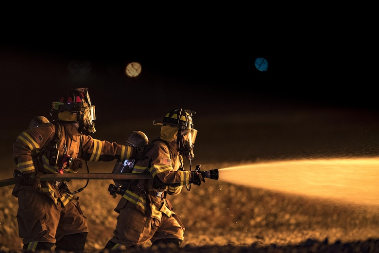 Firefighters from the 23d Civil Engineer Squadron advance towards a fire during nighttime, live-fire training, Jan. 10, 2017, at Moody Air Force Base, Ga. This training is an annual requirement for Moody firefighters and is just one of the ways they stay ready to protect people, property and the environment from fires and disasters. (U.S. Air Force photo by Staff Sgt. Ryan Callaghan)