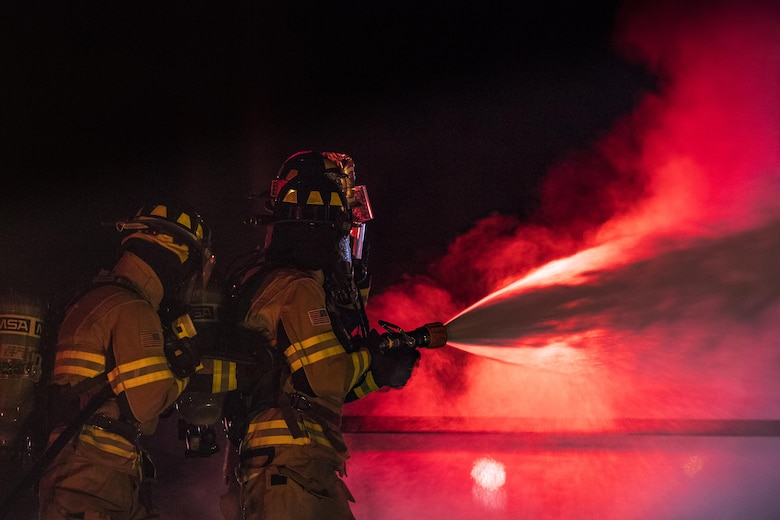 Firefighters from the 23d Civil Engineer Squadron douse a prop aircraft during nighttime, live-fire training, Jan. 10, 2017, at Moody Air Force Base, Ga. This training is an annual requirement for Moody firefighters and is just one of the ways they stay ready to protect people, property and the environment from fires and disasters. (U.S. Air Force photo by Staff Sgt. Ryan Callaghan)