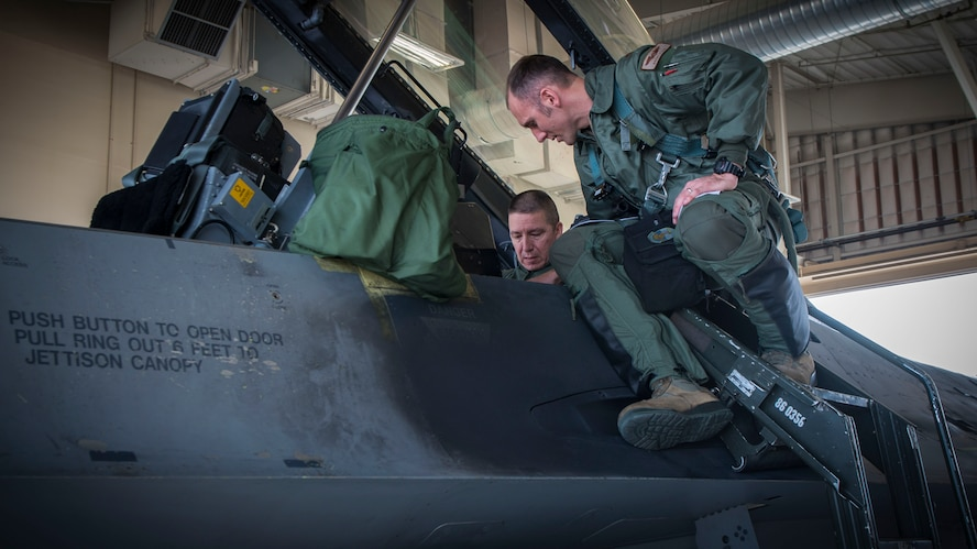 Maj. Brent Ellis, a fighter pilot with the 311th Fighter Squadron, instructs Brig. Gen. Eric Sanchez, the Commanding General at White Sands Missile Range, on basic flight procedures prior to a familiarization flight in an F-16 Fighting Falcon, at Holloman Air Force Base, N.M., on Jan. 9, 2017. Sanchez visited Holloman AFB to attend an airspace and mission brief related to Holloman and WSMR's ongoing partnership. Sanchez was offered a flight in an F-16 Fighting Falcon to gain a better understanding of the aircraft's mission and its capabilities. (U.S. Air Force photo by Airman 1st Class Alexis P. Docherty)