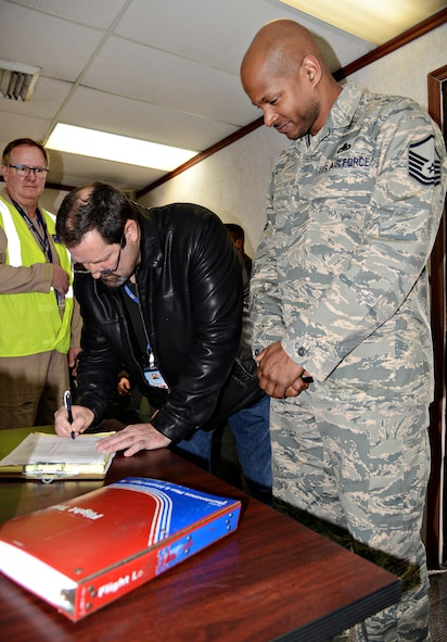 A representative from Boeing signs the paperwork transferring the first of 24 E-3 Sentry aircraft to undergo DRAGON cockpit modernization, back to the 552nd Air Control Wing.  Accepting for the 552nd ACW is Master Sgt. Maliek, 552nd Maintenance Group depot liaison. (Air Force photo by Kelly White)