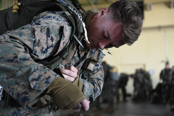 A Marine with the 3rd Reconnaissance Battalion, 3rd Marine Division, III Marine Expeditionary Force, straps a parachute to his body in preparation for a static line parachute drop on Jan. 11, 2017, at Yokota Air Base, Japan. The training ensures that jumpers and flight crew are ready to respond to real world events throughout the Indo-Asia Pacific region. (U.S. Air Force photo by Airman 1st Class Donald Hudson)