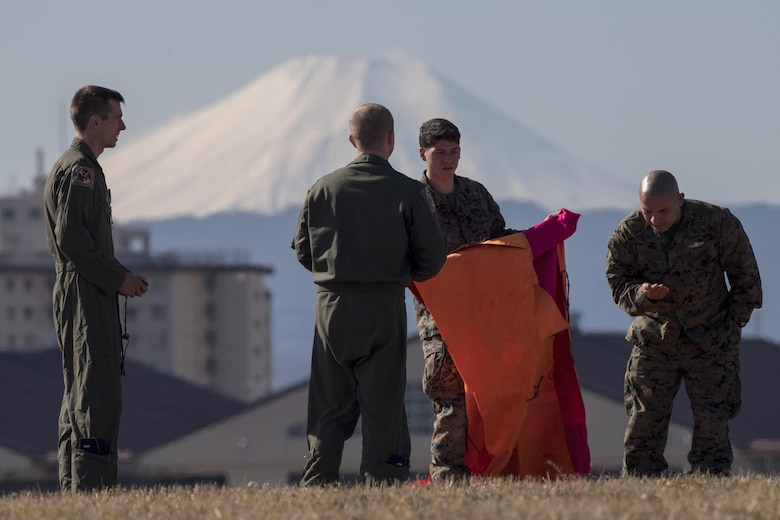 Airmen with the 36th Airlift Squadron and Marines with the 3rd Reconnaissance Battalion, 3rd Marine Division, III Marine Expeditionary Force set up an angle marker at Yokota Air Base, Japan, Jan. 10, 2017. III MEF Marines conducted weeklong jump training from an Air Force C-130 Hercules, assigned to the 36 AS. The training not only allowed the Marines to practice jumping, but it also allowed the Yokota aircrews to practice flight tactics and timed-package drops. (U.S. Air Force photo by Yasuo Osakabe/Released)