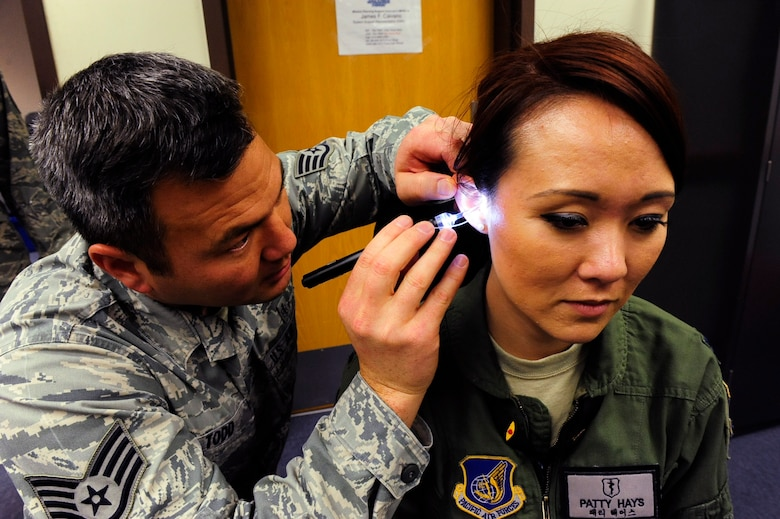 Staff Sgt. Edward Todd, 8th Medical Operations Squadron dental laboratory technician, inserts a tube into the ear of Capt. Patricia Hays, 8th Medical Operations Squadron aerospace and operational physiologist, to make an inner-ear mold for the Attenuating Custom Communications Earpiece System at Kunsan Air Base, Republic of Korea, Jan. 9, 2017. The ACCES device will significantly reduce surrounding ambient noise that pilots hear in the cockpit and increase the efficiency of radio communications. (U.S. Air Force photo by Staff Sgt. Chelsea Browning/Released)