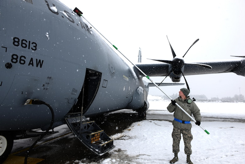 Airman 1st Class Jacob Taatjes, 86th Aircraft Maintenance Squadron crew chief, removes snow from a C-130J Super Hercules aircraft at Ramstein Air Base, Germany, Jan. 10, 2017. Continuous heavy snow persisted throughout the majority of the day, prompting snow removal operations throughout the base.. (U.S. Air Force photo by Airman 1st Class Joshua Magbanua)