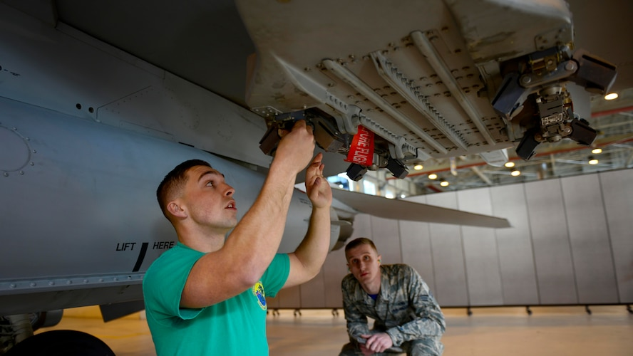 Airman 1st Class Waylon Scheirer, left, 31st Aircraft Maintenance Squadron weapons load crew member, prepares to load munitions on an F-16 Fighting Falcon while Senior Airman Michael Velasco, load competition judge, observes him during the annual load competition at Aviano Air Base, Italy on January 6, 2017. Each year, the squadron's top weapons load crew teams compete to be awarded the 31st Fighter Wing Best Load Crew of the Year award. (U.S. Air Force photo by Senior Airman Areca T. Bell)