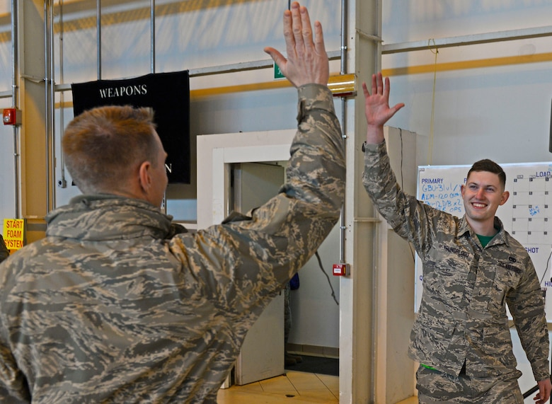 Airman 1st Class Matthew Youngblood, 31st Aircraft Maintenance Squadron weapons load crew member, high-fives Brig. Gen. Lance Landrum, 31st Fighter Wing commander, during the annual load competition at Aviano Air Base, Italy on Jan. 6, 2016. The three, 3-person teams were judged on their job knowledge, dress and appearance, and munitions load performance. (U.S. Air Force photo by Senior Airman Cary Smith)