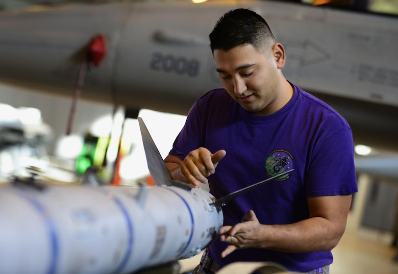 Staff Sgt. Patrick Peralta, 31st Aircraft Maintenance Squadron weapons load crew member, prepares to load an inert munition onto an F-16 Fighting Falcon during the annual load crew competition at Aviano Air Base, Italy on Jan. 6, 2016. Three 3-person teams competed for the 31st Fighter Wing's Best Load Crew of the Year award. (U.S. Air Force photo by Staff Sgt. Krystal Ardrey)