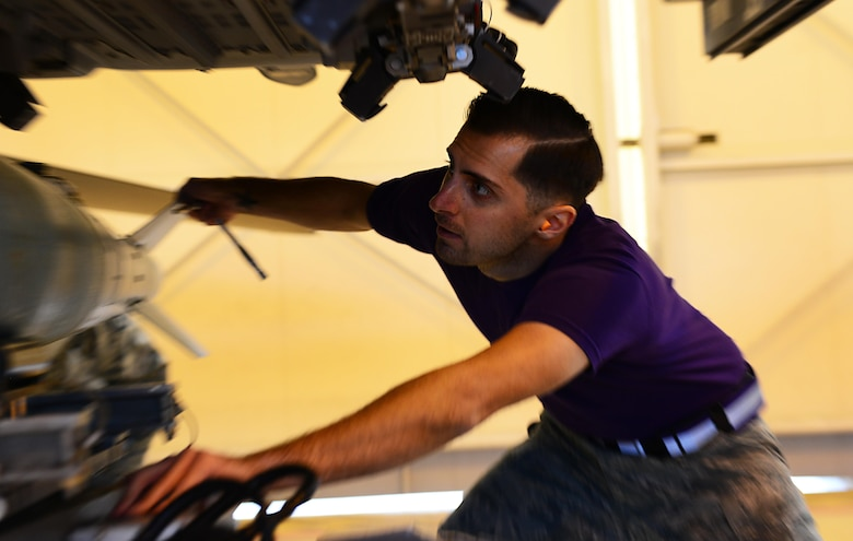 Staff Sgt. John Weiler, 31st Aircraft Maintenance Squadron weapons load crew chief, loads an inert munition onto an F-16 Fighting Falcon during a load crew competition at Aviano Air Base, Italy on Jan. 6, 2016. The three 3-person teams were judged on their job knowledge, dress and appearance, and munitions load performance. (U.S. Air Force photo by Staff Sgt. Krystal Ardrey)