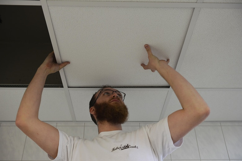 Lukas Denser, a carpenter, installs ceiling tiles in a restroom at the Northside Fitness Center on Ramstein Air Base, Germany, Jan. 13, 2017. The facility is undergoing renovations for its restrooms, locker rooms, and weight room. (U.S. Air Force photo by Airman 1st Class Joshua Magbanua)