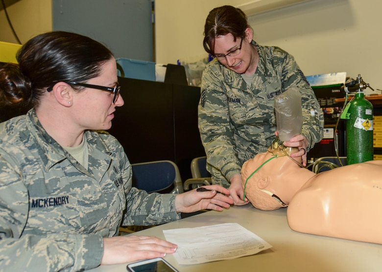 Staff Sgt. Jennifer A. McKendry, EMT instructor coordinator and Medical Technician with the 914th Aeromedical Staging Squadron, oversees Tech. Sgt. Megan L. Houseman, Medical Technician, 914 ASTS, as she demonstrates proper oxygen administration to a mannequin at the Niagara Falls Air Reserve Station, N.Y., January 12, 2016. Houseman was one of 26 military students who took part in a biannual training to recertify for the National Registry for Emergency Medical Technicians. The joint training involved members of the 914 ASTS, 914th Aeromedical Evacuation Squadron, 914th Fire Emergency Services, and the 107th Attack Wing. (U.S. Air Force photo by Peter Borys)