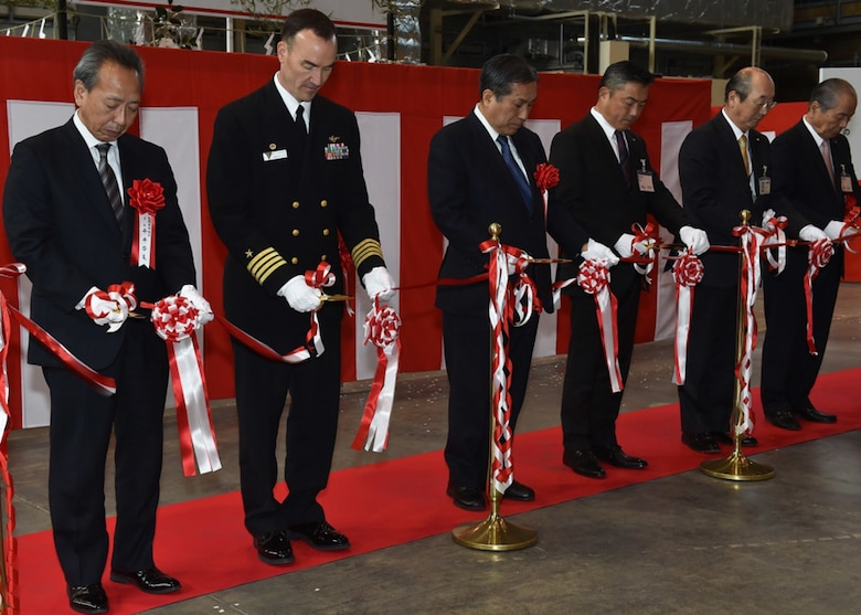 Capt. Matthew Edwards, commander, Fleet Readiness Center Western Pacific, joins Japanese city officials, business executives, and Japanese Ground Self-Defense Force (JGSDF) leaders in a ribbon cutting ceremony for the newly opened MV-22 Osprey, depot-level repair facility in JGSDF airfield, Camp. Kisarazu, Jan. 12, 2017. The facility is the first depot level facility for the MV-22 to open in Japan and will serve a critical role in keeping forward-deployed aircraft operational.