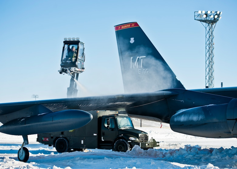 Airman 1st Class Samantha Coleman, 5th Aircraft Maintenance electronic countermeasures specialist, de-ices a B-52H Stratofortress at Minot Air Force Base, N.D., Jan. 11, 2017. A mixture of heated fluid and hot water is sprayed on the bombers prior to launching in cold weather conditions. 5th AMXS Airmen work in all weather conditions to provide B-52 global strike capabilities. (U.S. Air Force photo/Airman 1st Class J.T. Armstrong)