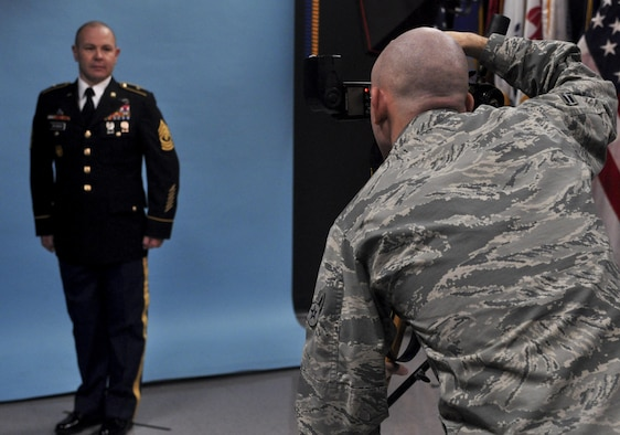 U.S. Air Force Airman 1st Class Randall Moose, 17th Training Wing Public Affairs photojournalist, takes an official photo of U.S. Army Master Sgt. Christopher Seymour, 344th military intelligence battalion, in the public affairs building on Goodfellow Air Force Base, Texas, January 12, 2016. The Public Affairs office takes official photos for all services on Goodfellow. (U.S. Air Force photo by 2nd Lt. Tisha Wilkerson/Released)