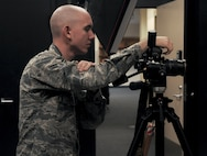 U.S. Air Force Airman 1st Class Randall Moose, 17th Training Wing Public Affairs photojournalist, prepares to take an official photo in the public affairs building on Goodfellow Air Force Base, Texas, January 12, 2016. The public affairs office takes regulation official photos for passports and promotions of all services on Goodfellow. (U.S. Air Force photo by 2nd Lt. Tisha Wilkerson/Released)