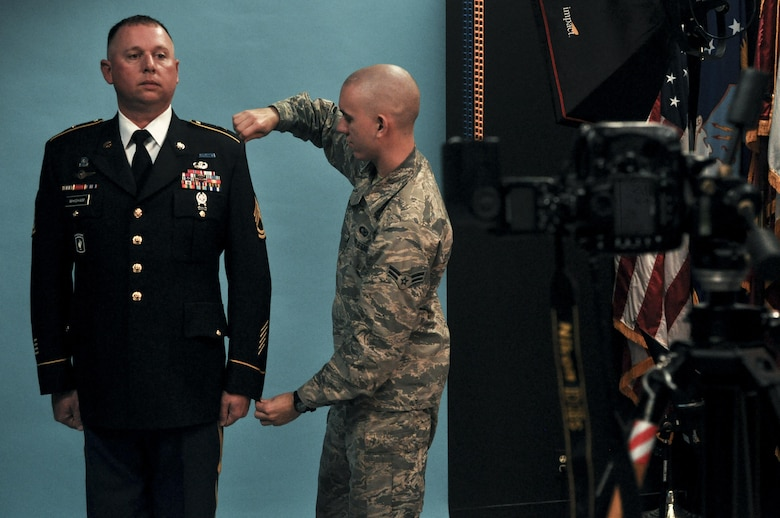 U.S. Air Force Airman 1st Class Randall Moose, 17th Training Wing Public Affairs photojournalist, adjusts the uniform of U.S. Army Sgt. 1st Class Corey Whigham, 344th military intelligence battalion, before taking an official photo in the public affairs building on Goodfellow Air Force Base, Texas, January 12, 2016. The Public Affairs office takes official photos for all services on Goodfellow. (U.S. Air Force photo by 2nd Lt. Tisha Wilkerson/Released)