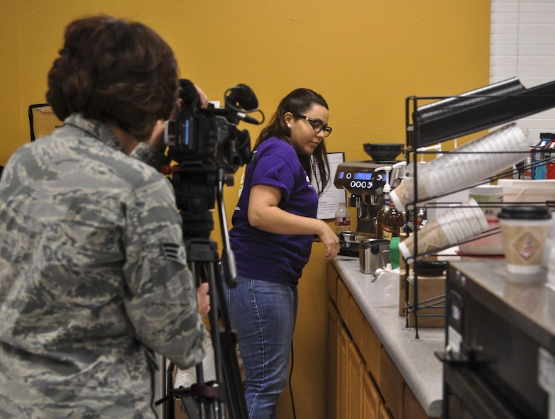 U.S. Air Force Senior Airman Megan Reed, 17th Training Wing Public Affairs broadcast journalist, gathers b-roll of the grand opening of a coffee shop on Goodfellow Air Force Base, Texas, January 13, 2016. The public affairs office covers events happening on or off base that impact Goodfellow. (U.S. Air Force photo by 2nd Lt. Tisha Wilkerson/Released)